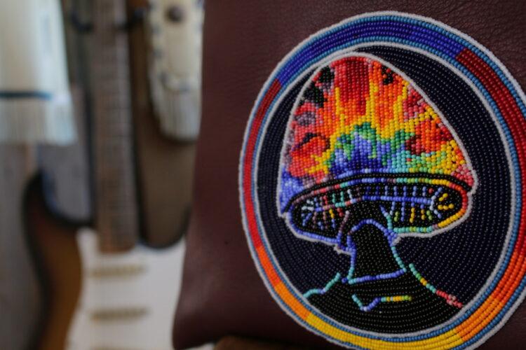 私物の鹿革トートバッグに好きなバンドのキノコのトレードマークをビーズワークした画像